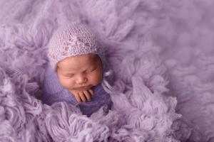 baby purple rug smiling